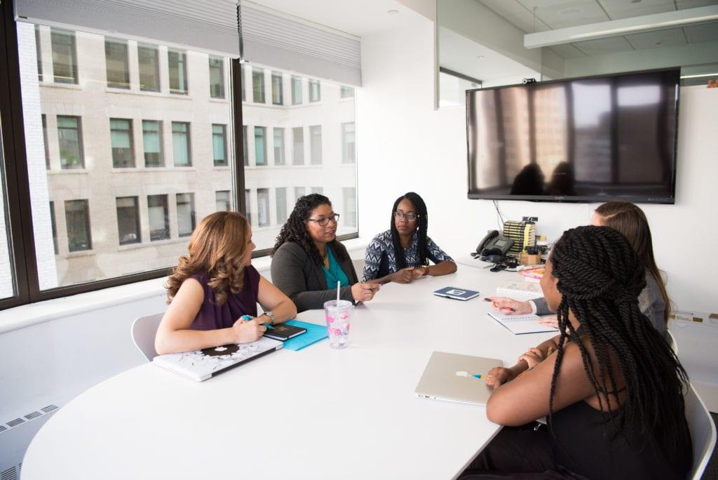 Group of five women gathering inside office